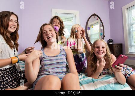 Les filles à l'aide de chambre à coucher en smartphone Banque D'Images