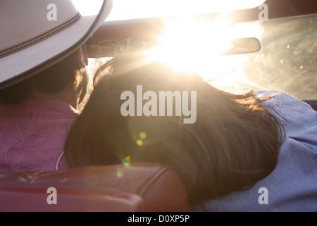Woman resting head on boyfriend's épaule alors qu'il entraîne dans la lumière du soleil Banque D'Images
