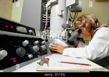 1970 Technicien de laboratoire à l'aide de MICROSCOPE ÉLECTRONIQUE FEMME Banque D'Images