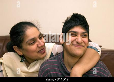 Maman avec ses 24 ans fille musulmane à la maison qui souffre de paralysie cérébrale, Londres, Royaume-Uni. Parution Banque D'Images