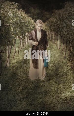 Une femme dans une robe de style édouardien blanc marche dans un vignoble Banque D'Images