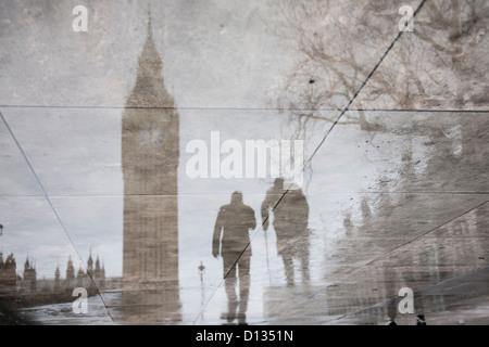 Reflet dans la chaussée mouillée de Maisons du Parlement et la statue de Winston Churchill avec silhouette d'un Banque D'Images