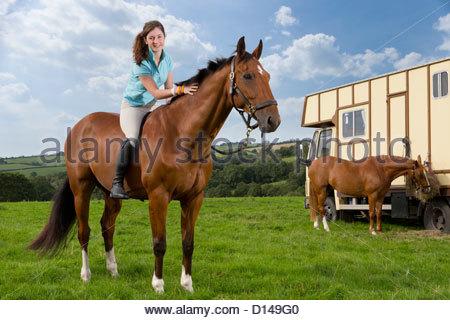 Portrait of smiling girl à cheval dans le champ Banque D'Images