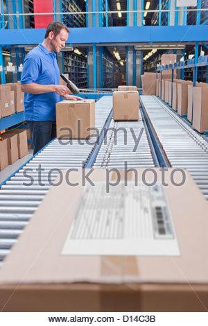 Travailleur avec lecteur de code à barres de balayage sur la courroie du convoyeur en entrepôt de distribution Banque D'Images