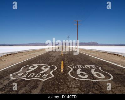 Route 66 sign painted sur désert de Mojave de sel de chaussée sur les routes. Banque D'Images