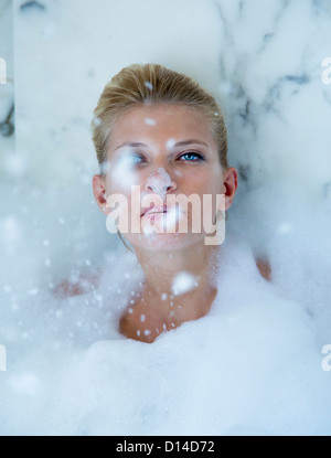 Woman playing in bubble bath Banque D'Images
