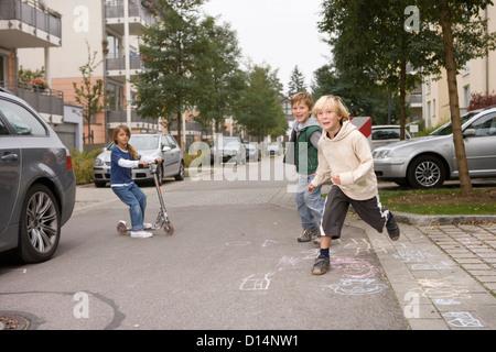 Les enfants jouant sur la rue de banlieue Banque D'Images