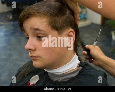 Adolescent garçon ayant une coupe de cheveux à la Hairdressers Banque D'Images