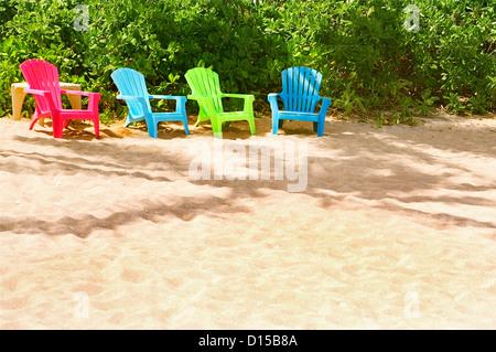 Hawaii, Kauai, Pila'a, Quatre chaises colorées reste sur le sable. Banque D'Images