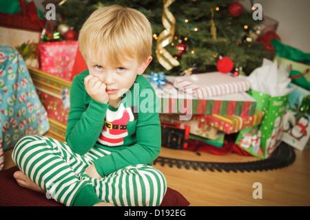 Grumpy Young Boy le matin de Noël près de l'arbre. Banque D'Images