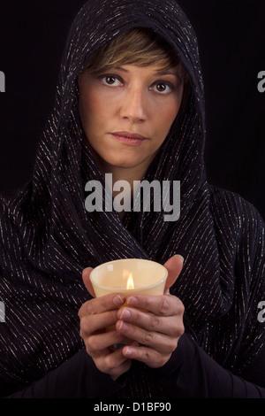 Belle jeune femme en cape noire tenant une bougie allumée dans ses mains et réfléchi à l'appareil photo. Portrait Banque D'Images