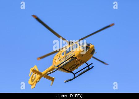 Écossais jaune Air Ambulance Service hélicoptère volant au-dessus d'une mission de sauvetage vu du dessous contre Banque D'Images