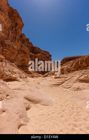 Des empreintes de pas sur une étroite piste de sable dans un désert montagneux région Banque D'Images