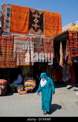Une femme en robe islamique devant les tapis traînant une entrée du souk de Marrakech, Maroc, Afrique du Nord Banque D'Images