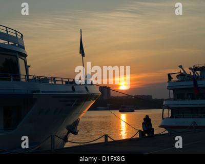 Jeune couple assis enlacés sur le quai de la rivière de Moscou entre deux navires de croisière à la lumière de soleil Banque D'Images