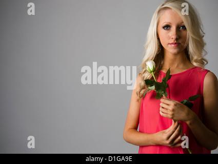 16 Un jeune homme de 17 ans slim blonde teenage girl holding, single white rose UK Banque D'Images