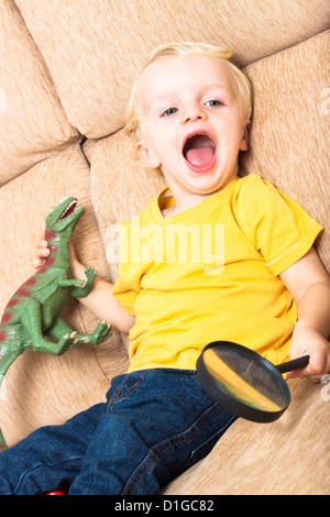 Close up of happy laughing enfant garçon jouant sur un canapé. Banque D'Images