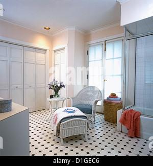 Les salles de bain en osier blanc et pouf avec coussins gris bleu courtepointe blanche plane sur grand ottoman peint Banque D'Images