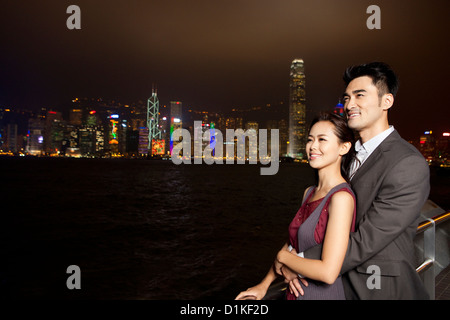 Happy young couple appréciant la vue de nuit sur le port de Victoria, Hong Kong Banque D'Images