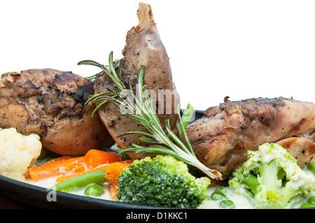La viande de lapin rôti et pommes de terre avec des légumes dans la plaque sur fond blanc Banque D'Images