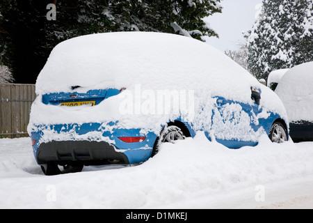 Dormansland, Surrey, Angleterre. Voiture garée sur la rue couverte de neige épais après blizzard. Banque D'Images