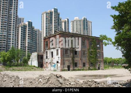 Un ancien entrepôt à l'abandon dans le centre de Shanghai avec les immeubles modernes construits tout autour de Banque D'Images