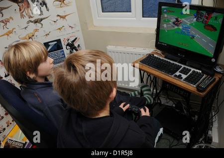 Deux blonde-haired young school boys se concentrer sur la lecture d'un ordinateur ou d'un Sony PlayStation jeu de course avec un dinosaure poster