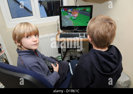 Deux jeunes aux cheveux blonds et des garçons jouent à l'école d'un ordinateur ou d'un jeu de course PlayStation de Sony