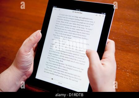 Une femme tourne la page d'un ebook sur l'iPad 4 application iBooks Banque D'Images
