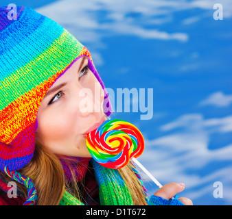 Photo de jolie fille de manger du sucre candy piscine en hiver, closeup portrait de belle femme portant chapeau coloré chaleureux