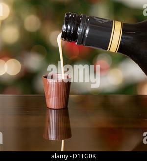 Irish Cream Liqueur laiteuse est versé dans le verre shot de chocolat avec arbre de Noël