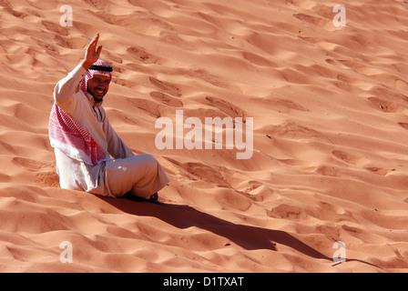 Homme portant un Keffieh rouge jordanien s'asseoir sur une dune de sable dans le Wadi Rum, Jordanie Banque D'Images