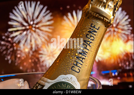 Fermer la vue sur bouteille de champagne frais sur la glace en vin avec une grande célébration partie d'artifice Banque D'Images