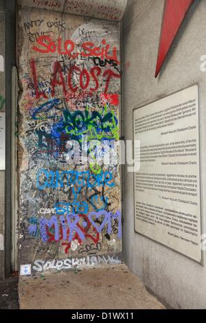 Un graffiti sur une section de mur original avec l'information en quatre langues à l'extérieur musée Checkpoint Banque D'Images