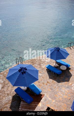 Des parasols et des chaises longues à l'seasite, Elounda, Agios Nikolaos, Crète, Grèce Banque D'Images