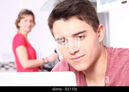 Jeune homme à l'aide d'un ordinateur portable, une femme est à l'arrière-cuisine. Banque D'Images