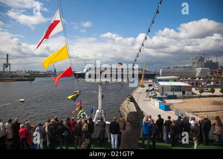 Les passagers d'une croisière MS Deutschland bienvenue l'arrivée de bateau de croisière Queen Mary 2 au centre de Banque D'Images