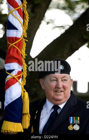 Un ancien combattant tenant l'Union Jack Flag, à des funérailles militaires. Banque D'Images