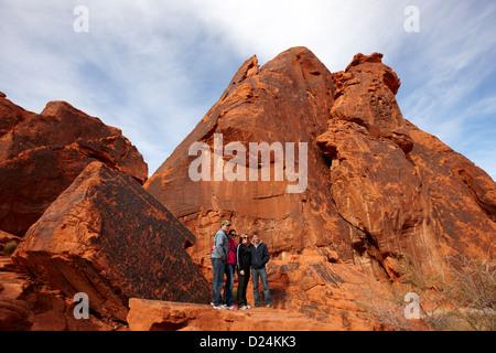 Les touristes posent devant des pétroglyphes sur atlatl rock grand Valley of Fire State Park nevada usa Banque D'Images