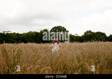 Une petite fille qui marche dans un champ, vue arrière Banque D'Images