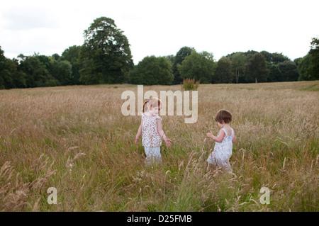 Deux petites filles jouant dans un champ en été Banque D'Images