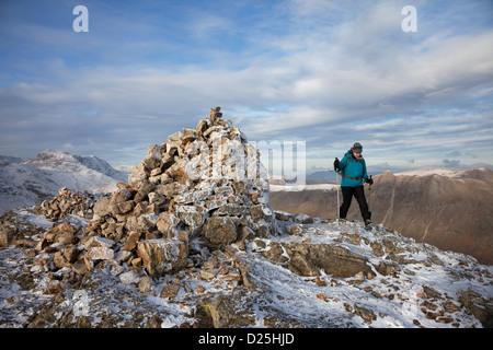 Walker sur le sommet du brochet de Blisco en hiver avec la montagne de l'ARC ont chuté à la gauche de la Cairn Lake District Cumbria UK