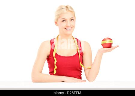 Jeune femme tenant une pomme et un ruban à mesurer, isolé sur fond blanc Banque D'Images