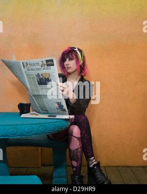 Jeune femme punk lire le journal tout en prenant un café dans un café à Virginia Beach, VA. Banque D'Images