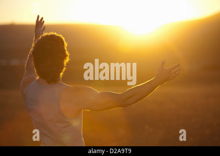 Man Standing in field at sunset Banque D'Images