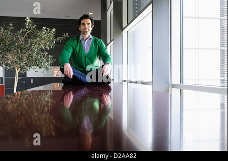 Businessman sitting on table Banque D'Images