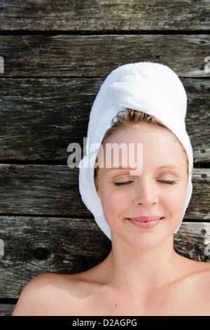 Smiling woman sur terrasse en bois Banque D'Images