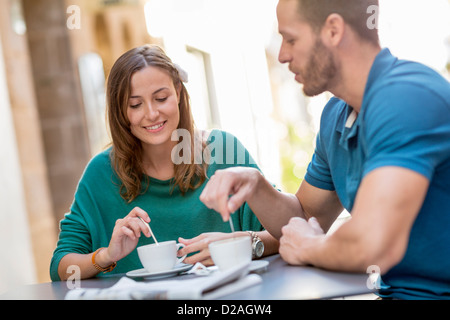 Couple having coffee at sidewalk cafe Banque D'Images