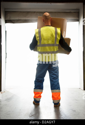 Worker carrying boxes in warehouse Banque D'Images