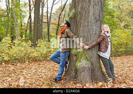 Couple holding hands autour de tree Banque D'Images